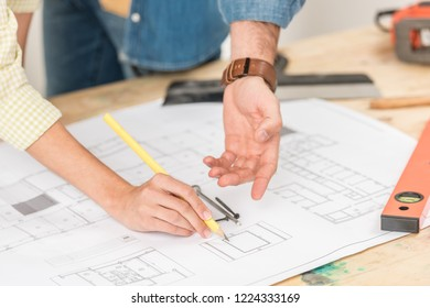 close-up partial view of young couple pointing at marking blueprint during renovation