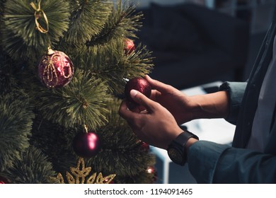 close-up partial view of young man decorating christmas tree at home