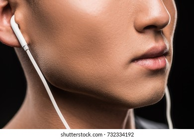 close-up partial view of young man listening music in earphone