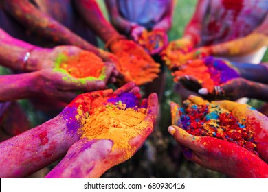 close-up partial view of young people holding colorful powder in hands at holi festival