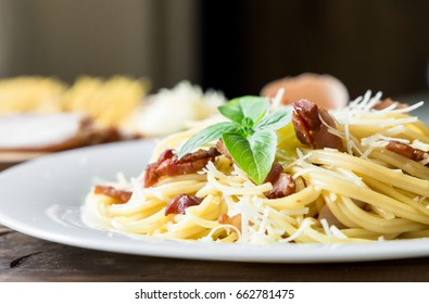 closeup of Pasta Carbonara. Spaghetti with bacon and parmesan cheese. Pasta Carbonara on white plate with parmesan on dark background. Italian food concept.