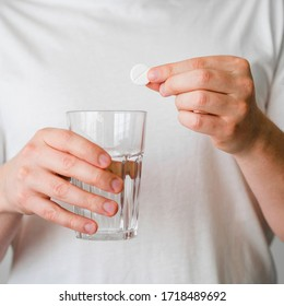 Close-up patient with round pill aspirin and water glass