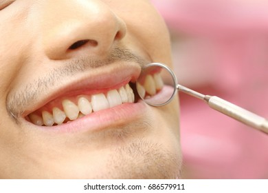 Close-up of patients open mouth during oral checkup with mirror near by, good healthcare in clinic room concept.
