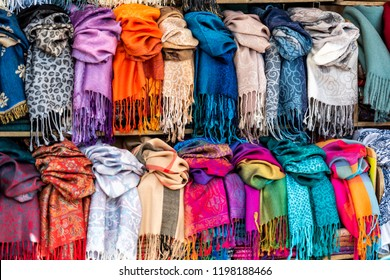 Closeup pattern of many scarves colorful vibrant colors, hanging, on display in shopping street market in Firenze, Florence, Italy in Tuscany