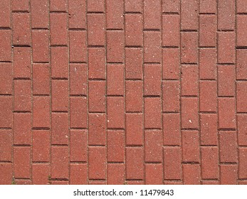 Closeup of the pattern of a red brick paved walkway.