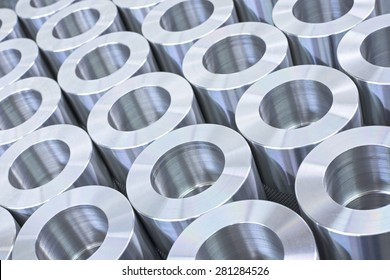 Closeup pattern of shiny circular precision stainless steel industrial machine parts arranged in rows