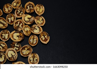 close-up pattern of walnut halves in the left side on a black background horizontal orientation