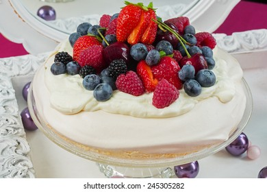 Closeup of Pavlova cake, decorated with fresh strawberries, blackberries, blueberries and cherry.