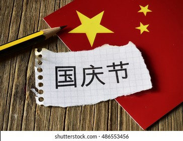 closeup of a peace of paper with the text National Day written in Chinese, a pencil and the flag of China, placed on a rustic wooden surface