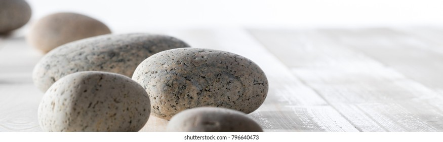 closeup of pebbles set on white wooden background for spirituality, ayurveda, mineral spa, yoga or mindfulness, long banner still life