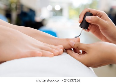 Close-up of pedicurist applying nail polish to the toenails, selective focus