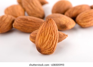 closeup peeled almonds isolated over white background