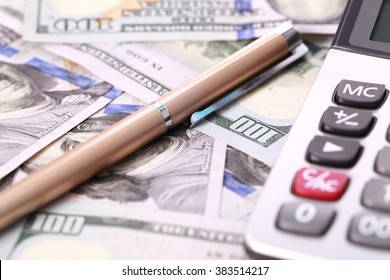 Close-up of pen and calculator on american dollars.