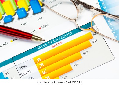 close-up of pen and financial growth charts, workplace businessman