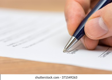 closeup of pen and human fingers  signing document