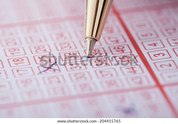 Closeup of pen marking numbers on lottery ticket