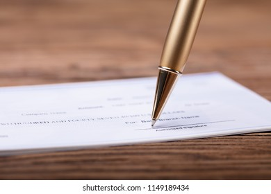Close-up Of Pen Signing Cheque On Wooden Desk