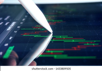 Closeup pen in trader 's hand point on chart trading screen.