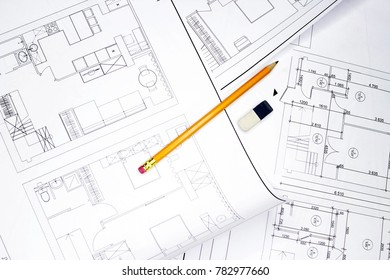 Close-up with a pencil above drawings with sketches of projects.