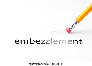 Closeup of pencil eraser and black embezzlement text. Embezzlement. Pencil with eraser.