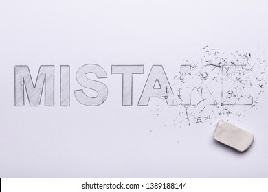 Close-up Of Pencil Eraser Erasing Mistake Word On White Paper