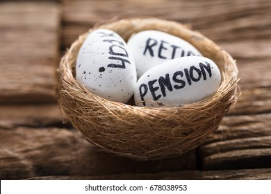 Closeup of pension  401K and retire written on white eggs in nest on wood