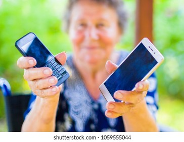Closeup of pensioner's hard choice between smartphone and old phone.