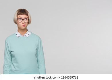 Closeup of pensive displeased young woman wears blue sweatshirt and spectacles looks displeased and thinking about her future job isolated over white background