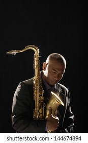 Closeup of a pensive man with saxophone looking down against black background