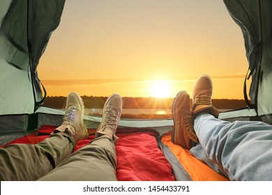 Closeup of people in camping tent with sleeping bags near river at sunset, view from inside
