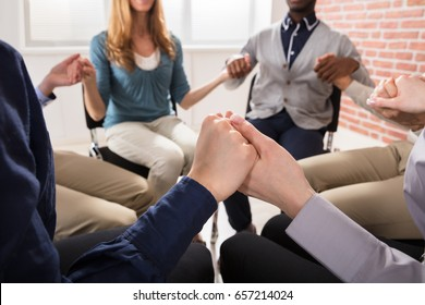 Close-up Of People Holding Each Others Hand Praying Together