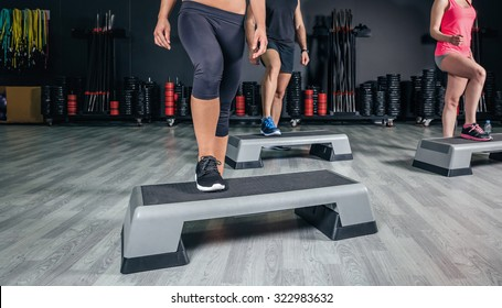 Closeup of people legs over step boards training in aerobic class on a fitness center. Sport and health concept.