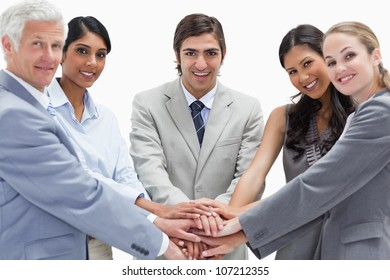 Close-up of people putting their hands on each others against white background