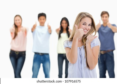 Close-up of people smiling and approving with one young woman in foreground against white background