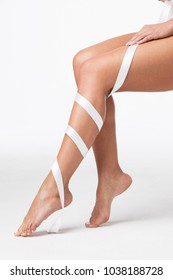 Closeup of perfect women's legs with white ribbon on white background