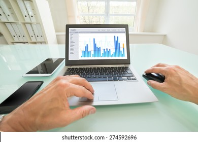 Close-up Of A Person Analyzing Graph On Laptop In Office