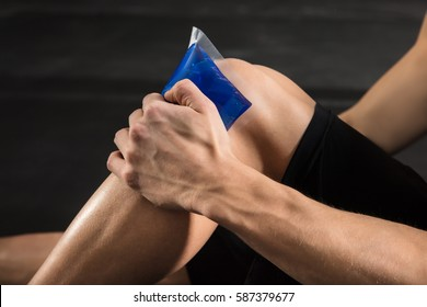 Close-up Of A Person Applying Ice bag On An Injured Knee In The Gym