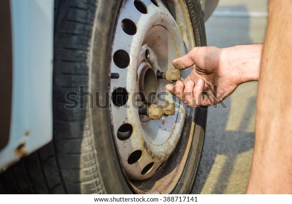 Closeup of person checking fixing bolts on vehicle tire with bare hands. outdoors photo