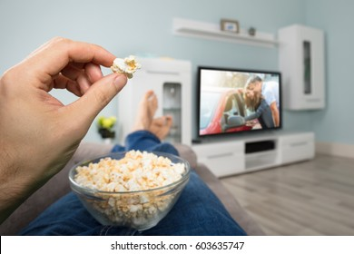 Close-up Of A Person Enjoy Watching Movie On Television While Eating Popcorn