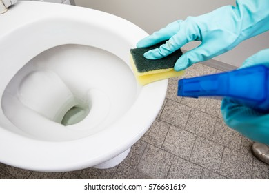 Close-up Of A Person Hand Cleaning Toilet Using Sponge In Bathroom
