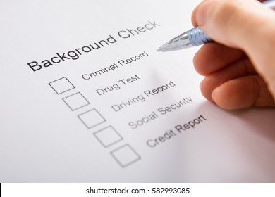 Close-up Of Person Hand Filling Background Check Form