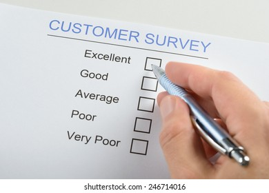 Close-up Of Person Hand Filling Customer Survey Form With Pen