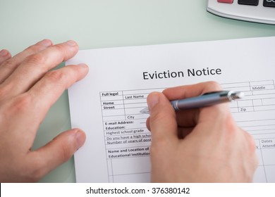 Close-up Of Person Hand Filling Eviction Notice Form