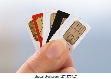 Close-up Of Person Hand Holding Four Phone Sim Cards