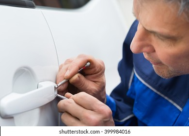 Close-up Of Person Hand Holding Lockpicker To Open Car Door