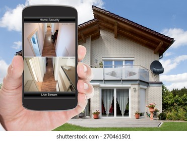 Close-up Of Person Hand Holding Mobile Phone With Home Security System