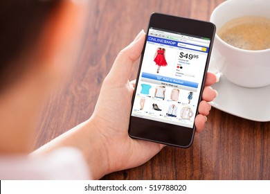 Close-up Of Person Hand Holding Mobilephone Doing Online Shopping On Wooden Desk