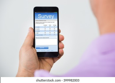Close-up Of Person Hand Holding Smartphone Showing Survey Form
