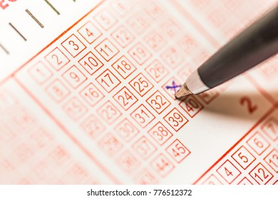 Close-up of person hand marking number on lottery ticket with pen