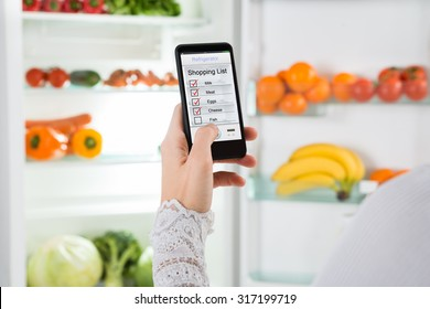Close-up Of Person Hand With Mobile Phone Showing Shopping List On Display